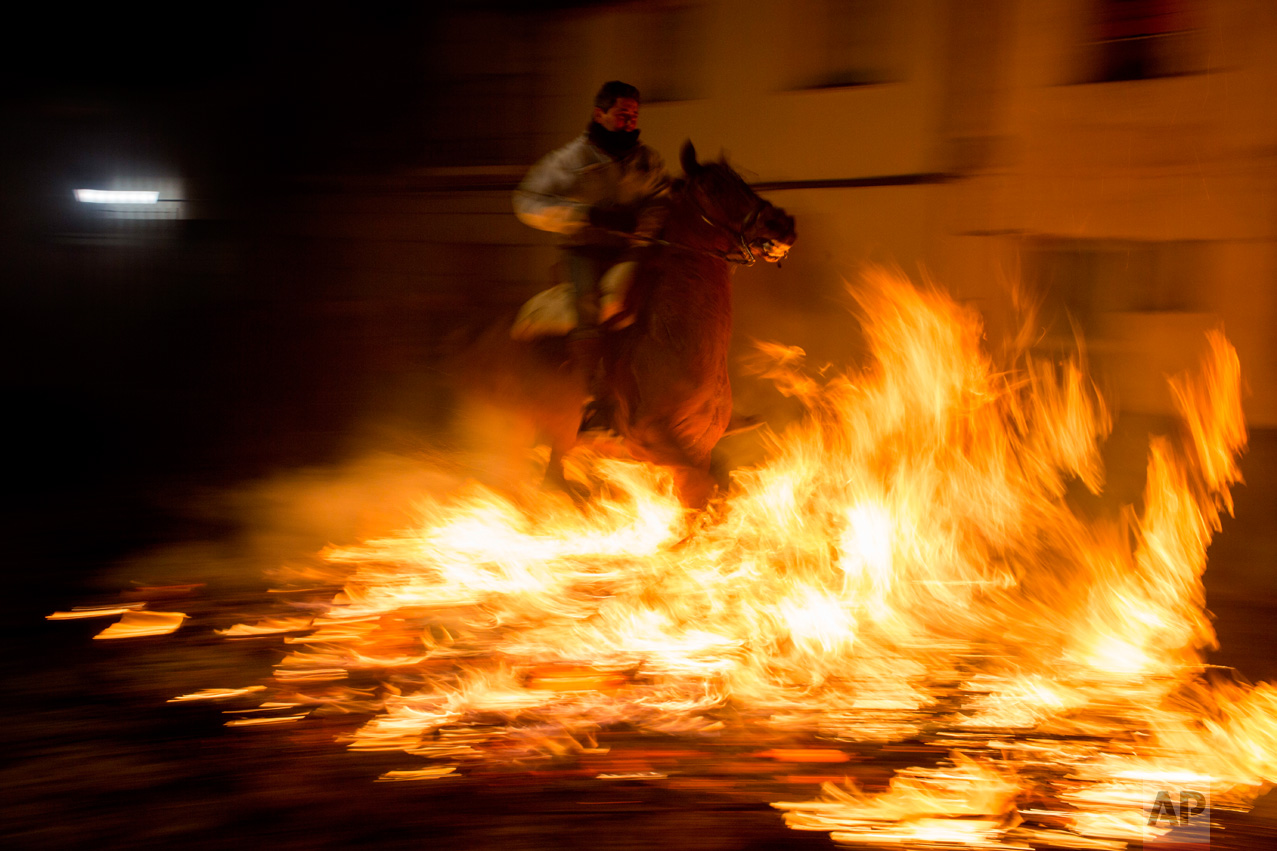 "A man rides a horse through a bonfire as part of a ritual in honor of Saint Anthony the Abbot, the patron saint of domestic animals, in San Bartolome de Pinares, about 100 km west of Madrid, Spain on Monday, Jan. 16, 2017. On the eve of Saint Anthony's Day, hundreds ride their horses through the narrow cobblestone streets of the small village of San Bartolome during the ""Luminarias,"" a tradition that dates back 500 years and is meant to purify the animals with the smoke of the bonfires and protect them for the year to come. (AP Photo/Emilio Morenatti)"