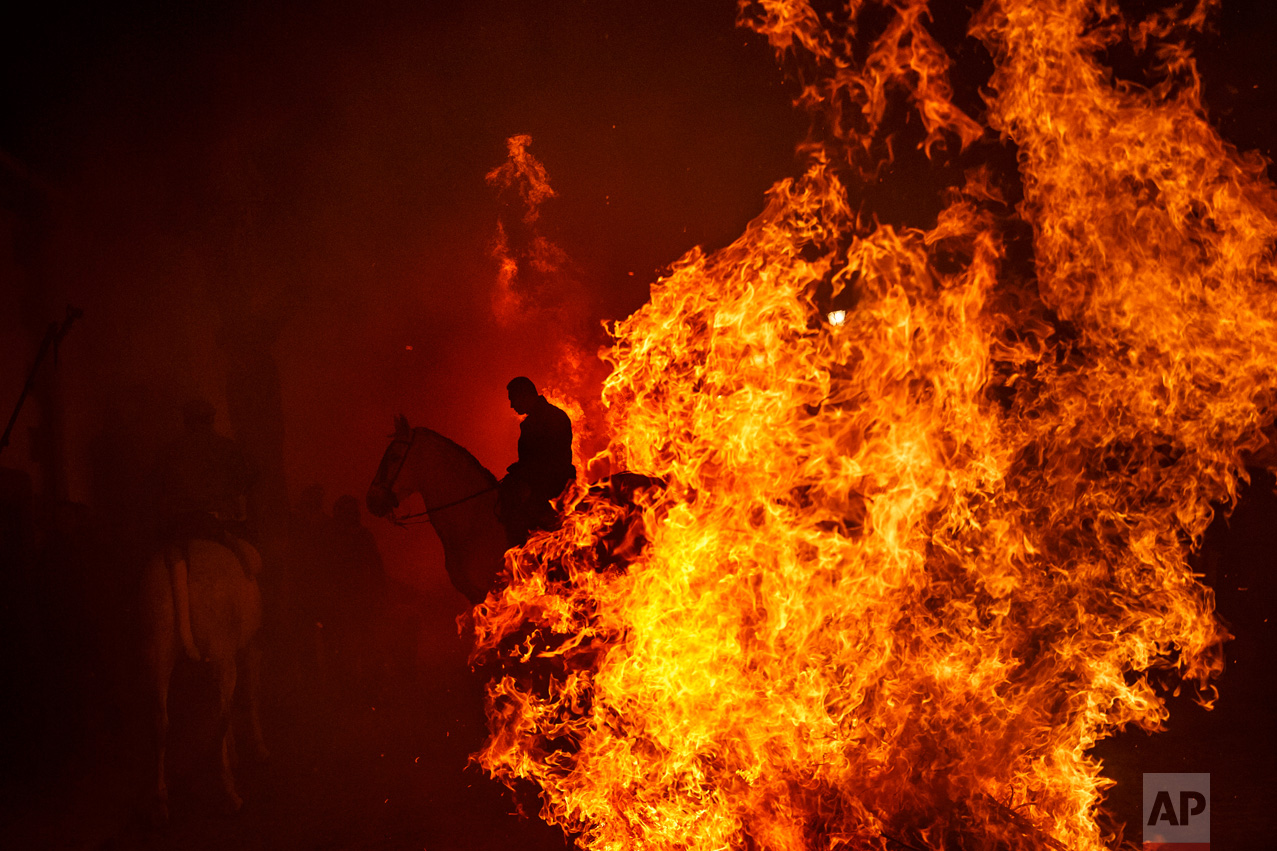 A man rides a horse by a bonfire as part of a ritual in honor of Saint Anthony the Abbot, the patron saint of domestic animals, in San Bartolome de Pinares, west of Madrid, Spain on Monday, Jan. 16, 2017.  (AP Photo/Daniel Ochoa de Olza)