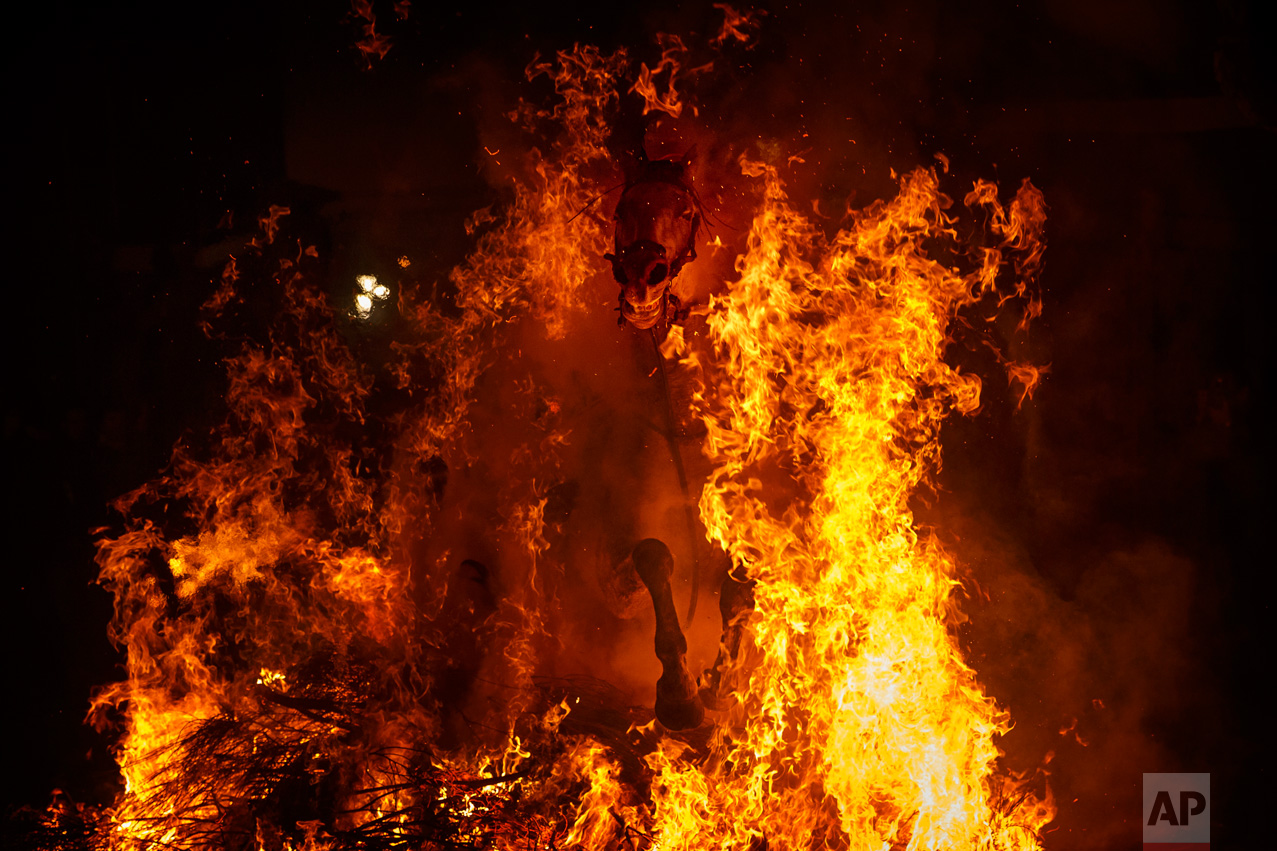 A man rides a horse through a bonfire as part of a ritual in honor of Saint Anthony the Abbot, the patron saint of domestic animals, in San Bartolome de Pinares, west of Madrid, Spain on Monday, Jan. 16, 2017. (AP Photo/Daniel Ochoa de Olza)