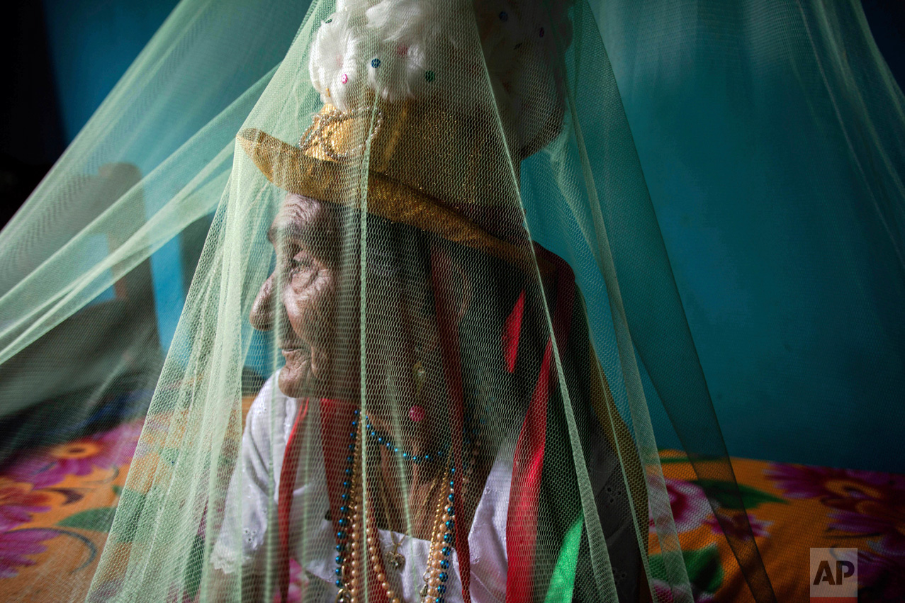 """This Dec. 19, 2016 photo shows Clara Padilha Gomes preparing spiritually for the Marujada religious celebration, in honor of St. Benedict, at her home in the fishing town of Braganca, Brazil. Gomes, 77, said she participates to give thanks for her son. """"As long as I'm alive, I will be devoted,"""" she said. """"A person has to have faith."""" (AP Photo/Eraldo Peres)"""