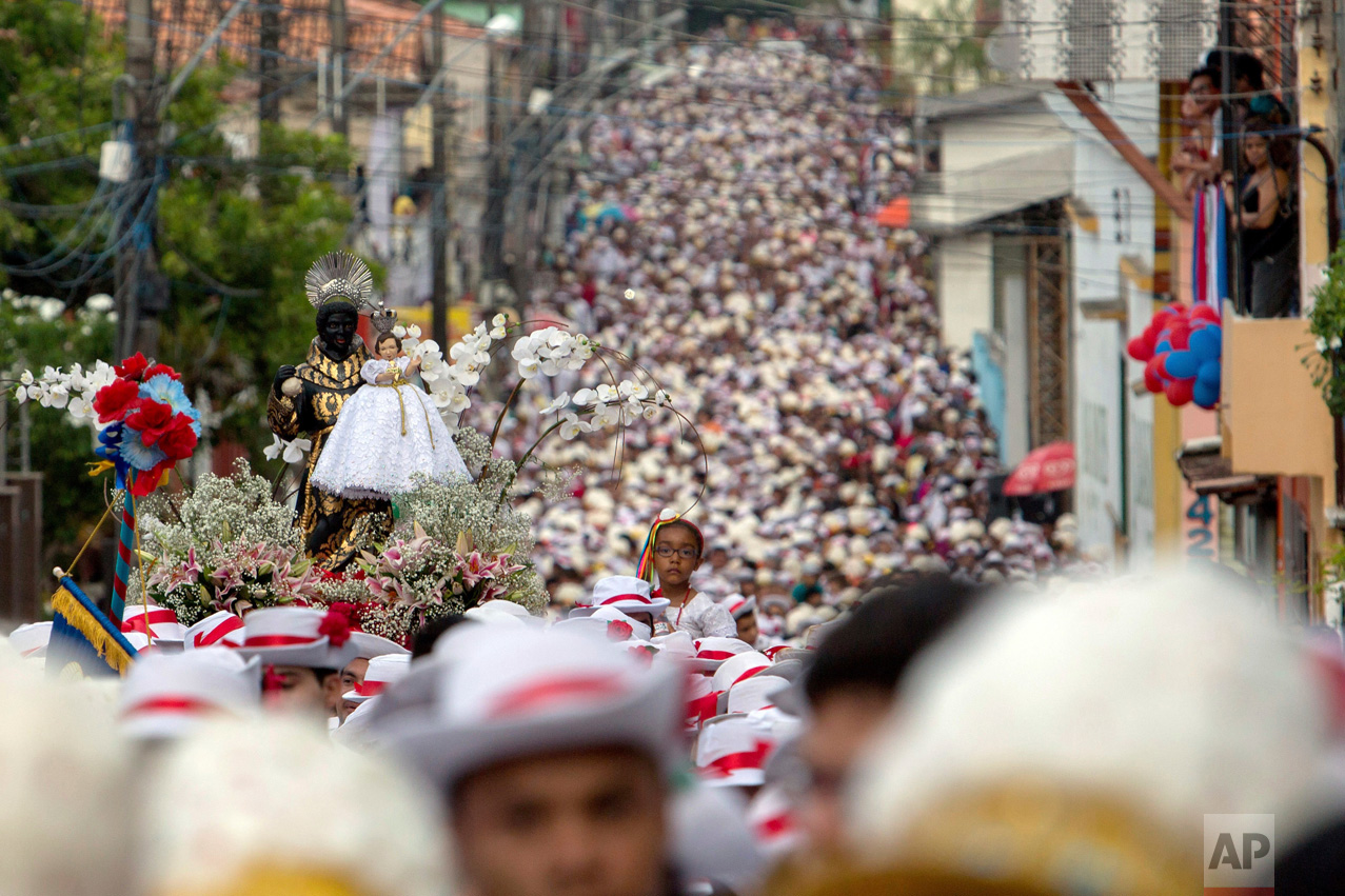 This Dec. 26, 2016 photo shows a procession in honor of St. Benedict filling a street in the fishing town of Braganca, Brazil during Marujada religious celebrations. Started in 1798, the event mixes indigenous, African and Portuguese traditions. (AP Photo/Eraldo Peres)