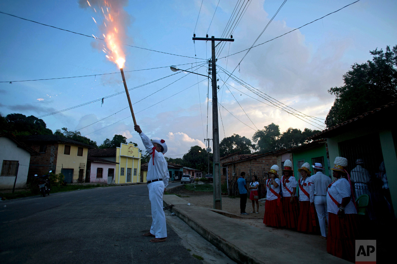 This Dec. 26, 2016 photo shows captain Jose Batista launching a firecracker during Marujada religious celebrations in honor of St. Benedict in the fishing town of Braganca, Brazil. The tradition started when black slaves persuaded their masters to let them form a brotherhood to pay homage to St. Benedict. (AP Photo/Eraldo Peres)