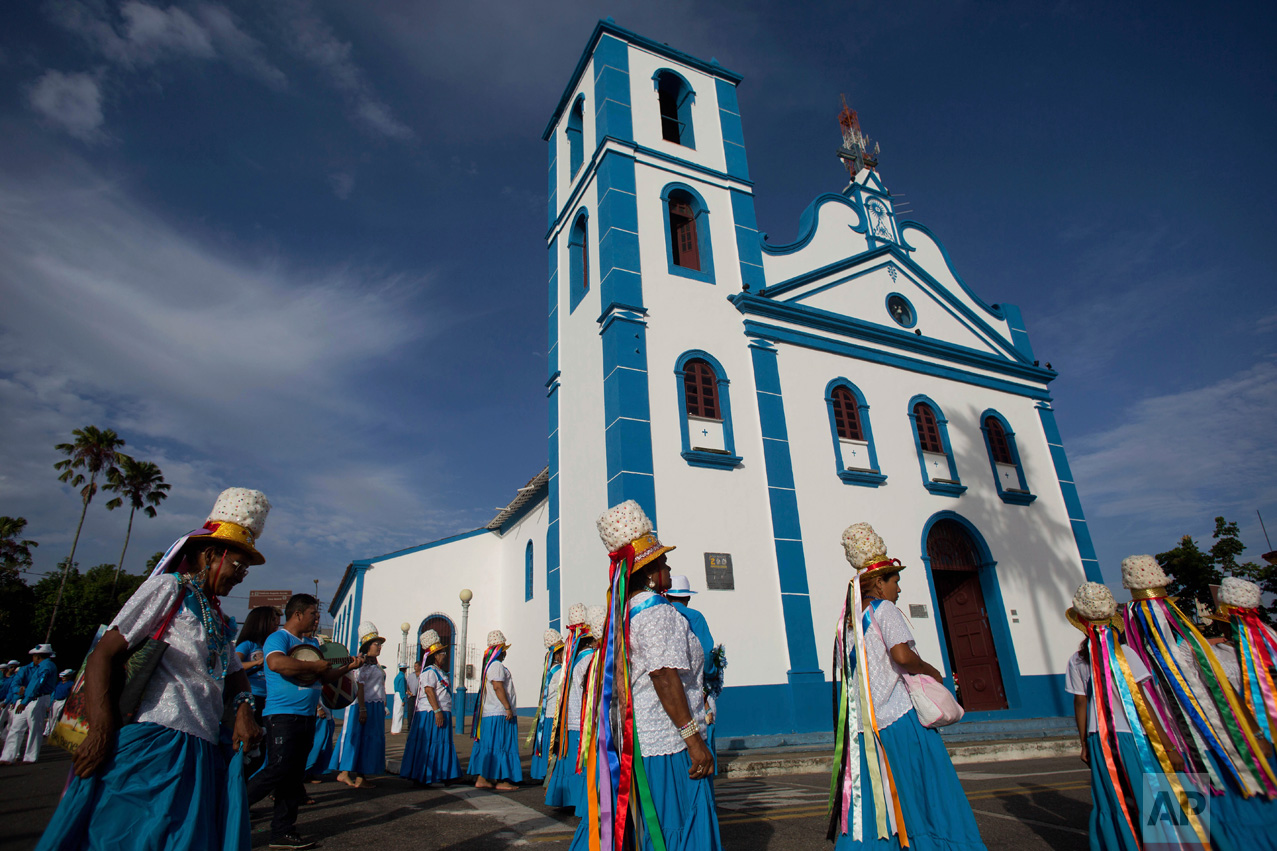 This Dec. 25, 2016 photo shows women in procession outside Saint Benedict Church during Marujada religious celebrations in honor of the Catholic Saint in the fishing town of Braganca, Brazil. For the procession, women wear blue skirts and white shirts and don white circular feathered, hats streaming colorful ribbons. (AP Photo/Eraldo Peres)