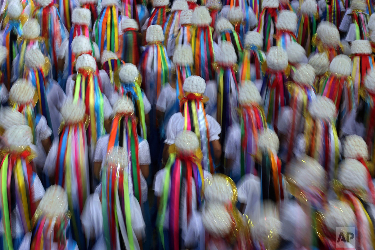 This Dec. 18, 2016 photo shows women wearing feathered hats with colorful ribbons performing the Retumbao dance during Marujada religious celebrations in honor of St. Benedict in the fishing town of Braganca, Brazil. Arriving at the church, some participants spend the day dancing Lundu, a couple's dance that originated in Angola and involves spinning in circles. (AP Photo/Eraldo Peres)