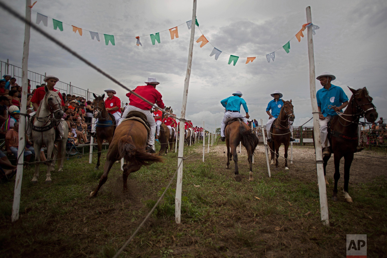 """This Dec. 25, 2016 photo shows young cowboys competing in the Cavalhada, using small sticks and rings, during Marujada religious celebrations in honor of St. Benedict in the fishing town of Braganca, Brazil. Started in 1798, the """"Marujada"""" religious celebration mixes indigenous, African and Portuguese traditions. (AP Photo/Eraldo Peres)"""