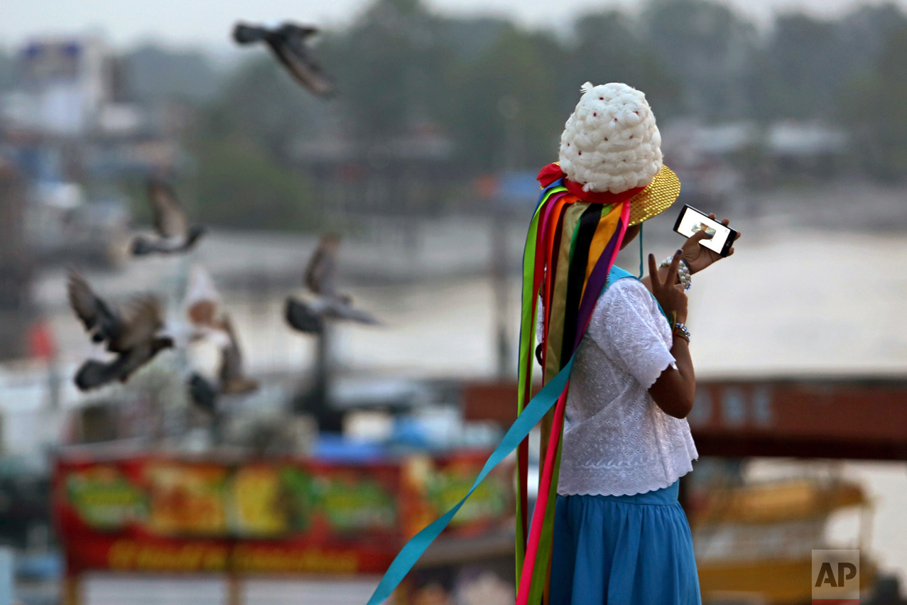 This Dec. 25, 2016 photo shows a girl in costume taking a selfie at the port in the fishing town Braganca, Para state, Brazil. This small city in northern Brazil pays tribute to St. Benedict with dance, horse competition and colorful costume. (AP Photo/Eraldo Peres)