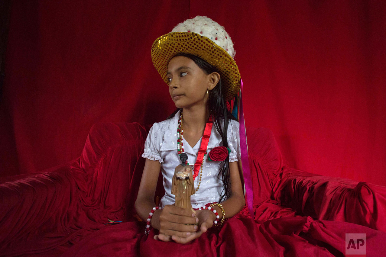 This Dec. 19, 2016 photo shows Sabrina Correia Aviz holding a statuette of St. Benedict inside her home, before the start of Marujada religious celebrations in the fishing town of Braganca, Brazil. Started in 1798, the Marujada religious celebration mixes indigenous, African and Portuguese traditions. (AP Photo/Eraldo Peres)
