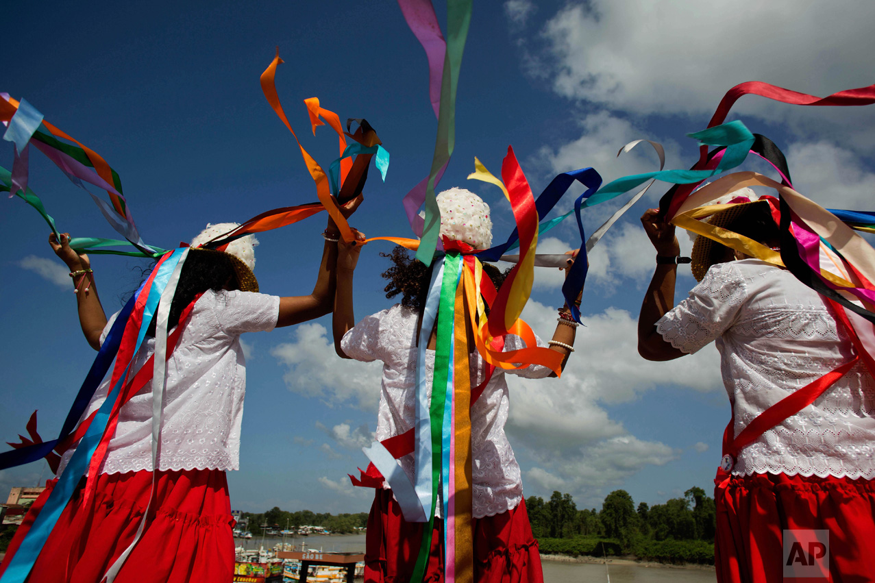 This Dec. 26, 2016 photo shows women at the port wearing feathered hats with multi-colored ribbons before the start of a procession honoring Saint Benedict during Marujada religious celebrations in the fishing town of Braganca, Brazil. Locals say the annual celebration, which started in 1798, is a way to show appreciation and make good on promises for miracles received. (AP Photo/Eraldo Peres)