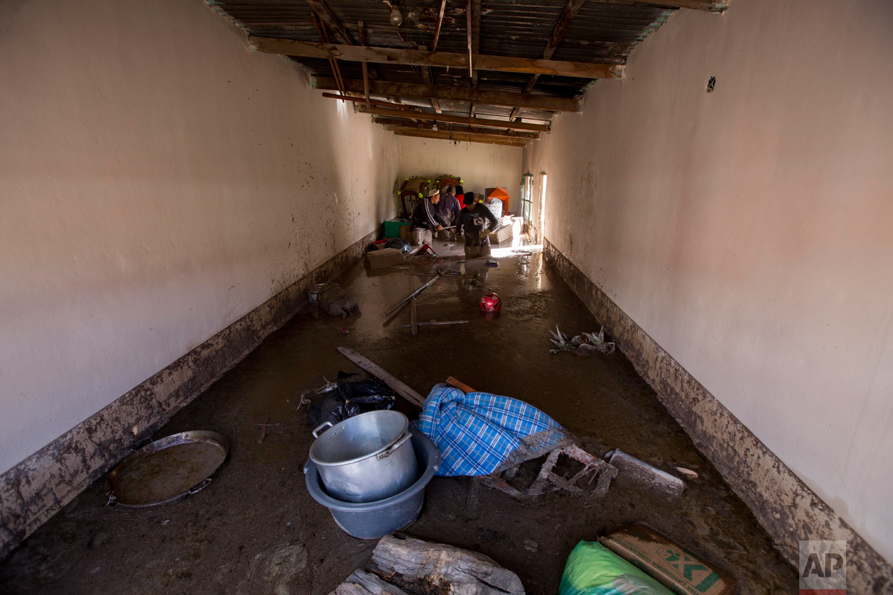 In this Jan. 13, 2017 photo, a resident begins the clean up of his mud flooded home in the town of Volcan, Jujuy province, Argentina. That town was covered by a mudslide a week ago after heavy rains hit the area. (Gianni Bulacio/Infoto via AP)