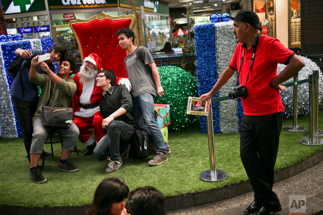 In this Dec. 18, 2016 photo, people take a selfie with Santa Claus as photographer Luis Maldonado waits for more clients at a mall in Santiago, Chile. Maldonado, the last remaining photographer in the main square of the Chilean capital still using a wooden box camera, has taken on other jobs to make ends meet. (AP Photo/Esteban Felix)