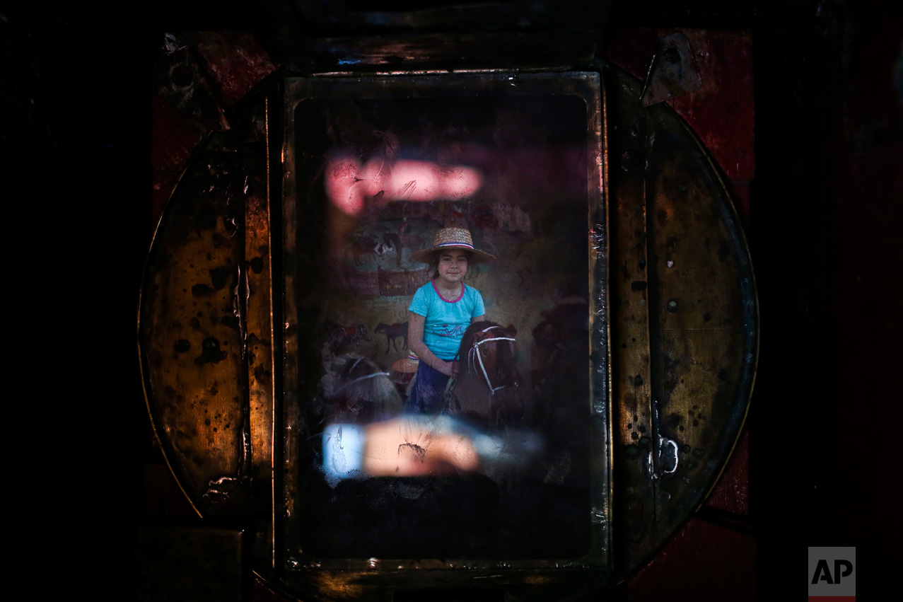 In this Sept. 4, 2016 photo, a girl getting her portrait made on a stuffed horse fills the viewfinder of Luis Maldonado's old wooden old box camera, during a fair marking Independence Day in Santiago, Chile. Maldonado believes box photography could be revived in Chile and wants to help raise awareness about the art form. (AP Photo/Esteban Felix)