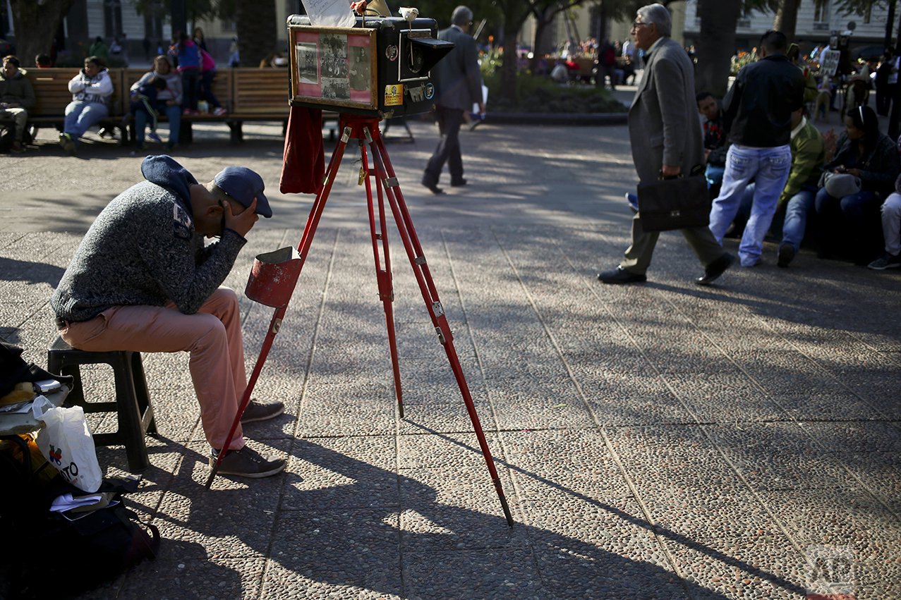 In this Sept. 1, 2016 photo, photographer Luis Maldonado waits for clients by his old wooden box camera in Plaza de Armas in Santiago, Chile. Clients are scarce, with days, even weeks, passing before someone asks him to create a portrait with the old-fashioned camera. (AP Photo/Esteban Felix)