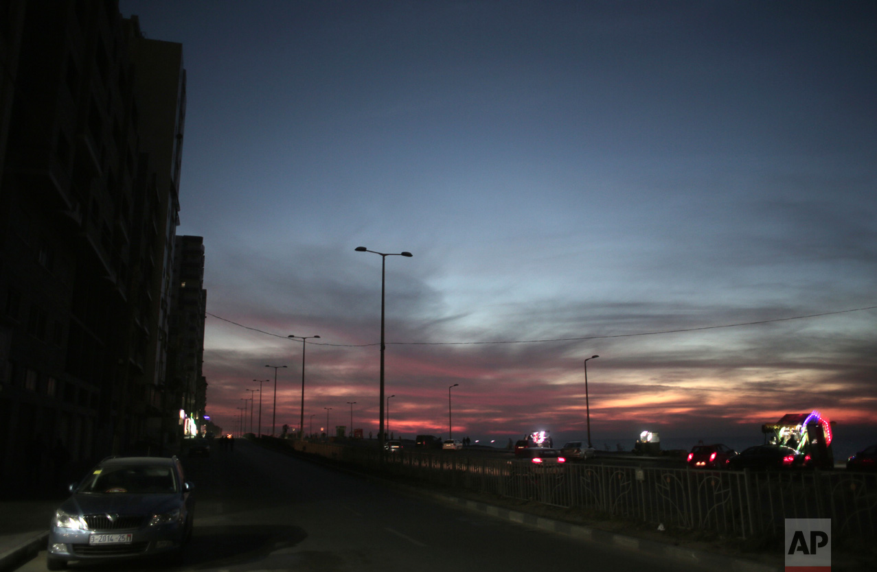 In this Monday, Jan. 16, 2017 photo, Palestinian vendors attach lights to their carts, on the right side of a dark road, during a power cut as the sun sets over Gaza City. (AP Photo/ Khalil Hamra)