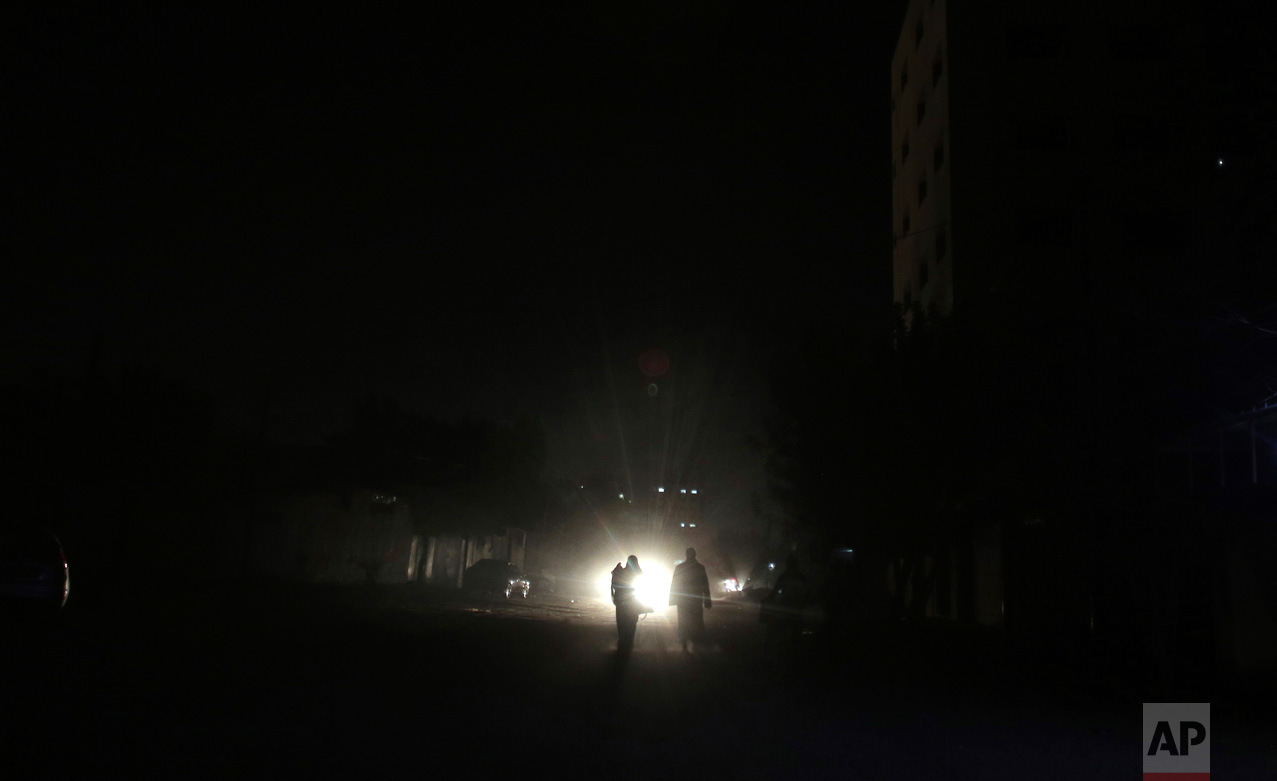 In this Monday, Jan. 16, 2017 photo, Palestinians walk on a dark street during the power cut in Gaza City. At night, large swaths of the Gaza Strip plunge into darkness - the result of chronic and worsening power outages. In crowded city streets, the only source of light comes from the headlights of passing cars. The power shortages are the worst to hit Gaza since Hamas seized control of the territory 10 years ago. (AP Photo/ Khalil Hamra)
