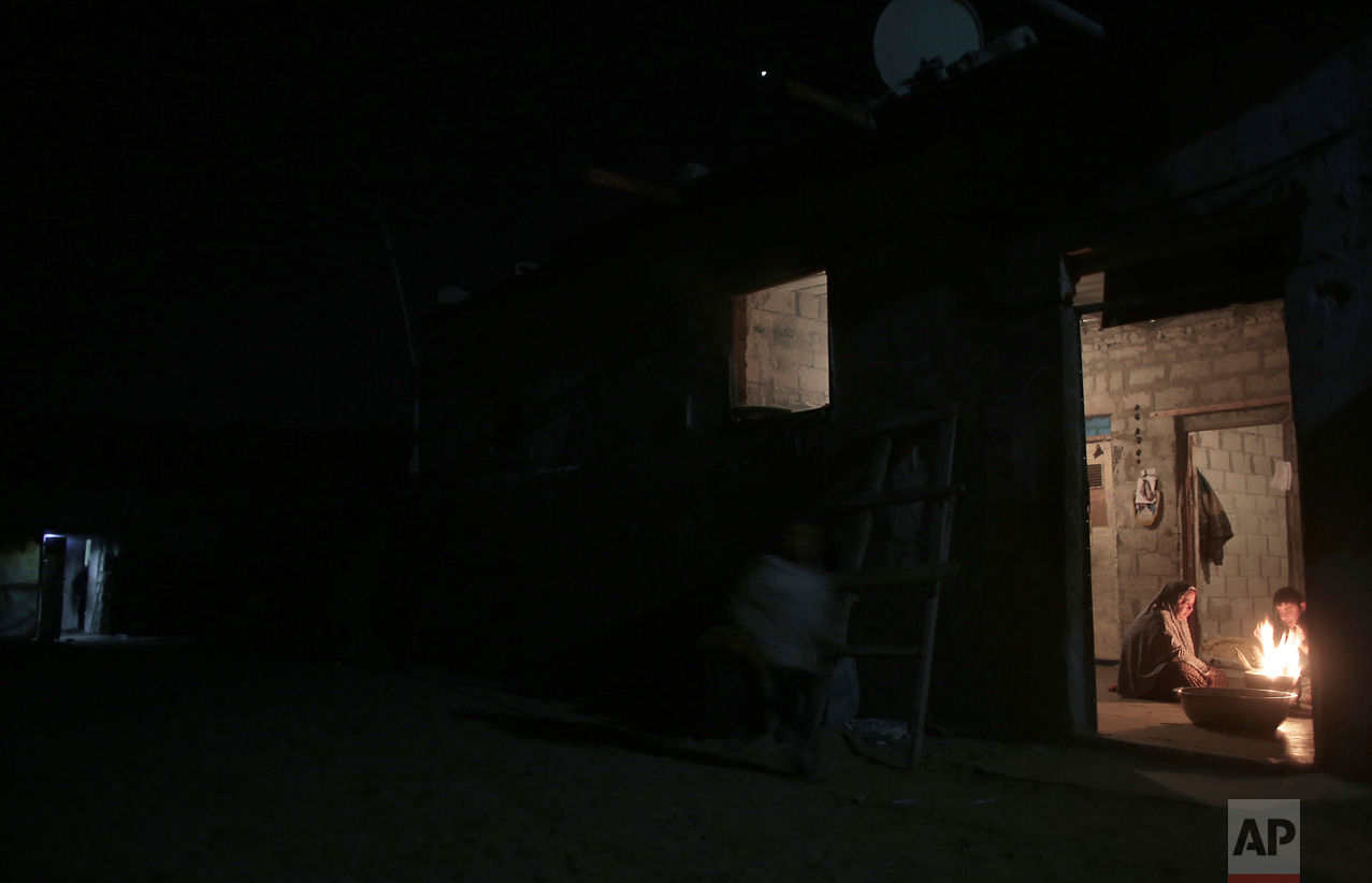 In this Sunday, Jan. 15, 2017 photo, a Palestinian family warm themselves up with a fire inside their makeshift house during the power cut in a poor neighborhood in town of Khan Younis in the southern Gaza Strip.(AP Photo/ Khalil Hamra)