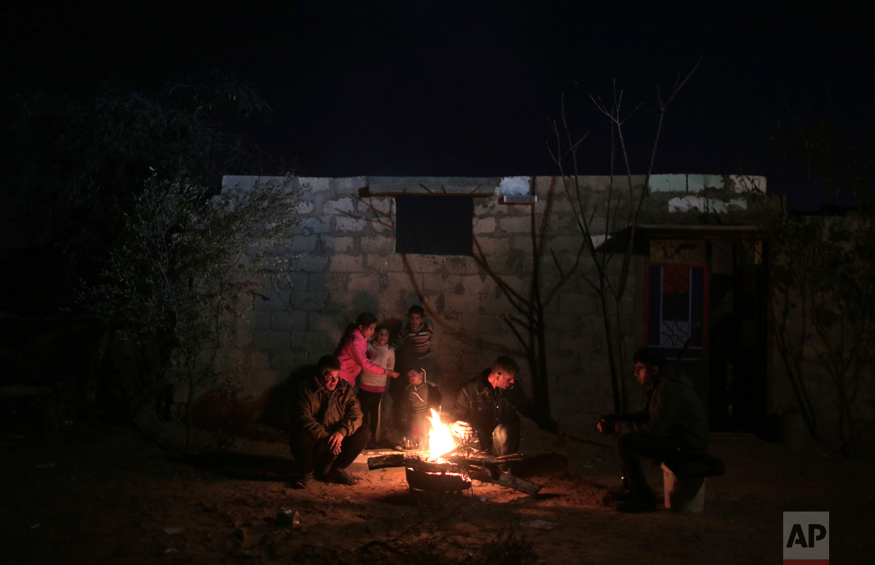 In this Sunday, Jan. 15, 2017 photo, a family warm themselves up with a fire outside their makeshift house during the power cut in a poor neighborhood in town of Khan Younis in the southern Gaza Strip. (AP Photo/ Khalil Hamra)