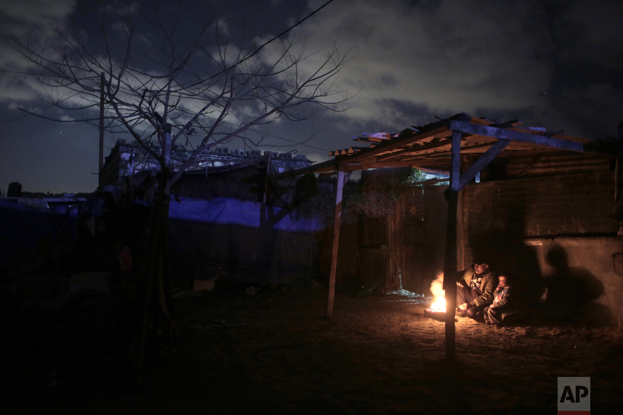 In this Sunday, Jan. 15, 2017 photo, a Palestinian family warm themselves up with a fire outside their makeshift house during the power cut in a poor neighborhood in town of Khan Younis in the southern Gaza Strip. (AP Photo/ Khalil Hamra)