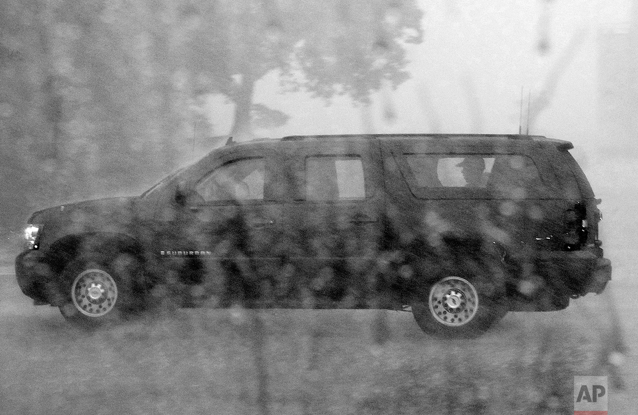 President Barack Obama is seated in his sports utility vehicle as he is driven from Andrews Air Force Base, Md., as his round of golf was ended by a sudden storm, Sunday, July 25, 2010. (AP Photo/Charles Dharapak)