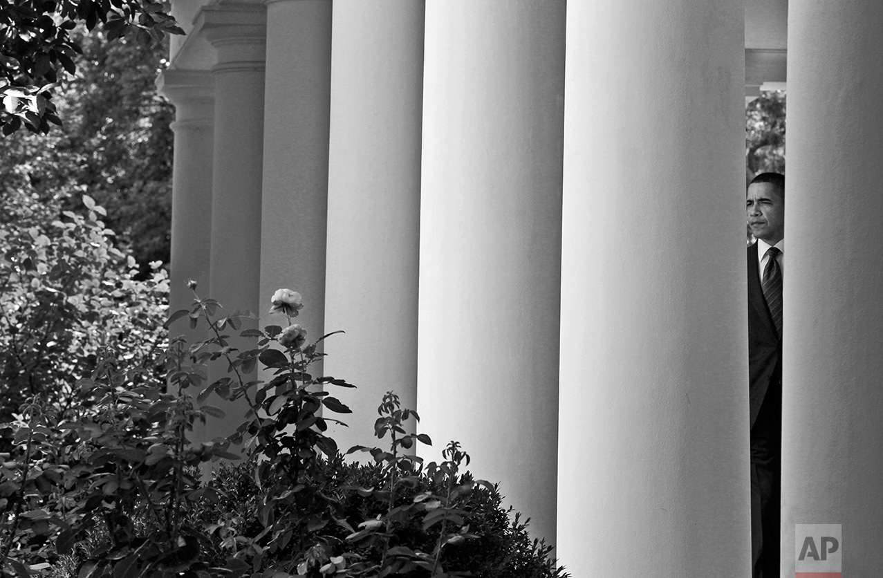 President Barack Obama is seen between the columns of the West Wing colonnade at the White House in Washington, Monday, July 26, 2010. (AP Photo/Charles Dharapak)