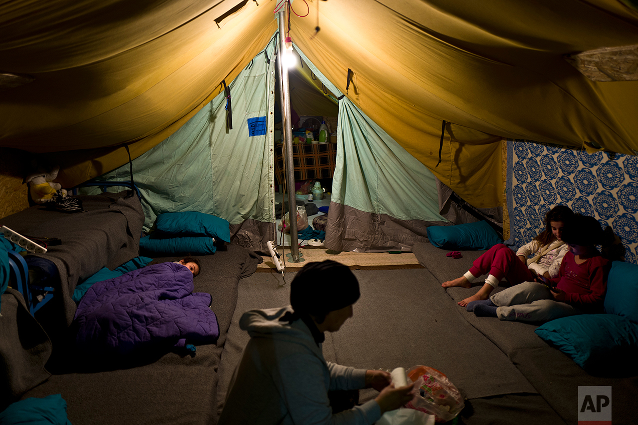 In this Tuesday, Jan. 17, 2017 photo, a Syrian refugee woman works inside her tent while her daughter left lies on the ground and her other daughter play with her friends, in Kalochori refugee camp on the outskirts of the northern Greek city of Thessaloniki. (AP Photo/Muhammed Muheisen)