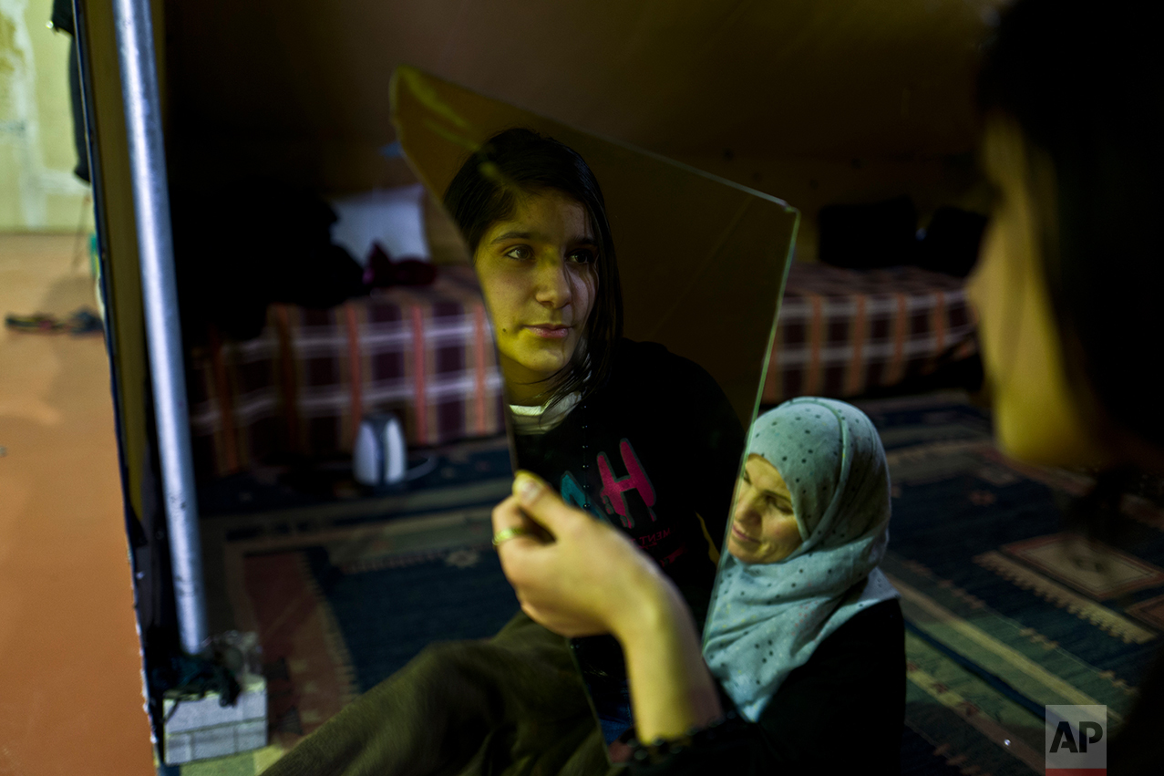 In this Tuesday, Jan. 17, 2017 photo, Syrian refugee Kulnawaz Youssef, 13, looks at herself in a mirror at her tent in Kalochori refugee camp on the outskirts of the northern Greek city of Thessaloniki. Many migrants living in this warehouse tent camp and another one nearby are feeling burned out. They try to keep busy as they dream of a better life in Western Europe and not let boredom or depression set in. (AP Photo/Muhammed Muheisen)