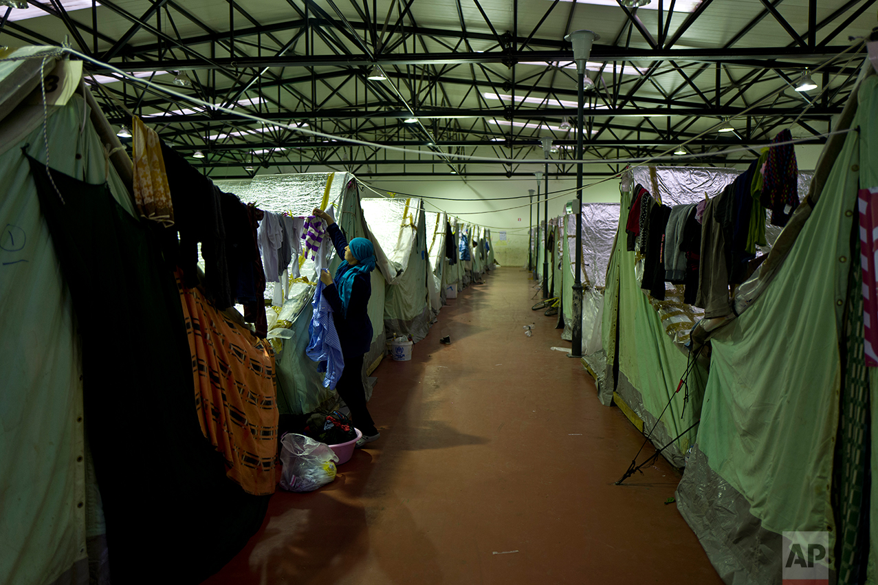 In this Tuesday, Jan. 17, 2017 photo, a Syrian refugee woman hangs her laundry outside her tent in Kalochori refugee camp on the outskirts of the northern Greek city of Thessaloniki. Because of a harsh winter and bitter cold, many migrants rarely venture out and away from the monotony and fluorescent lights hanging overhead. (AP Photo/Muhammed Muheisen)