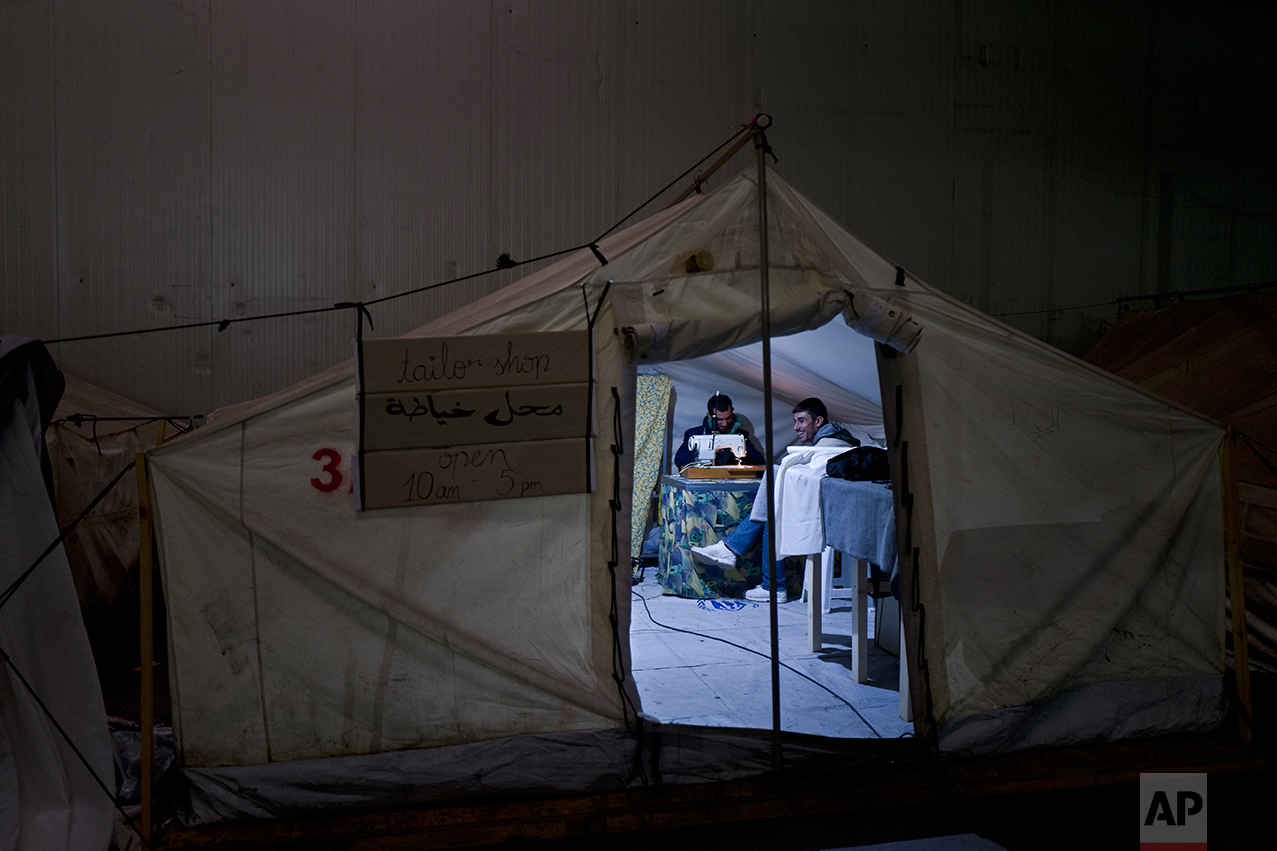 In this Wednesday, Jan. 18, 2017 photo, a Syrian refugee man repairs clothes at a tailor shop set up in a tent in Frakapor refugee camp on the outskirts of the northern Greek city of Thessaloniki. (AP Photo/Muhammed Muheisen)