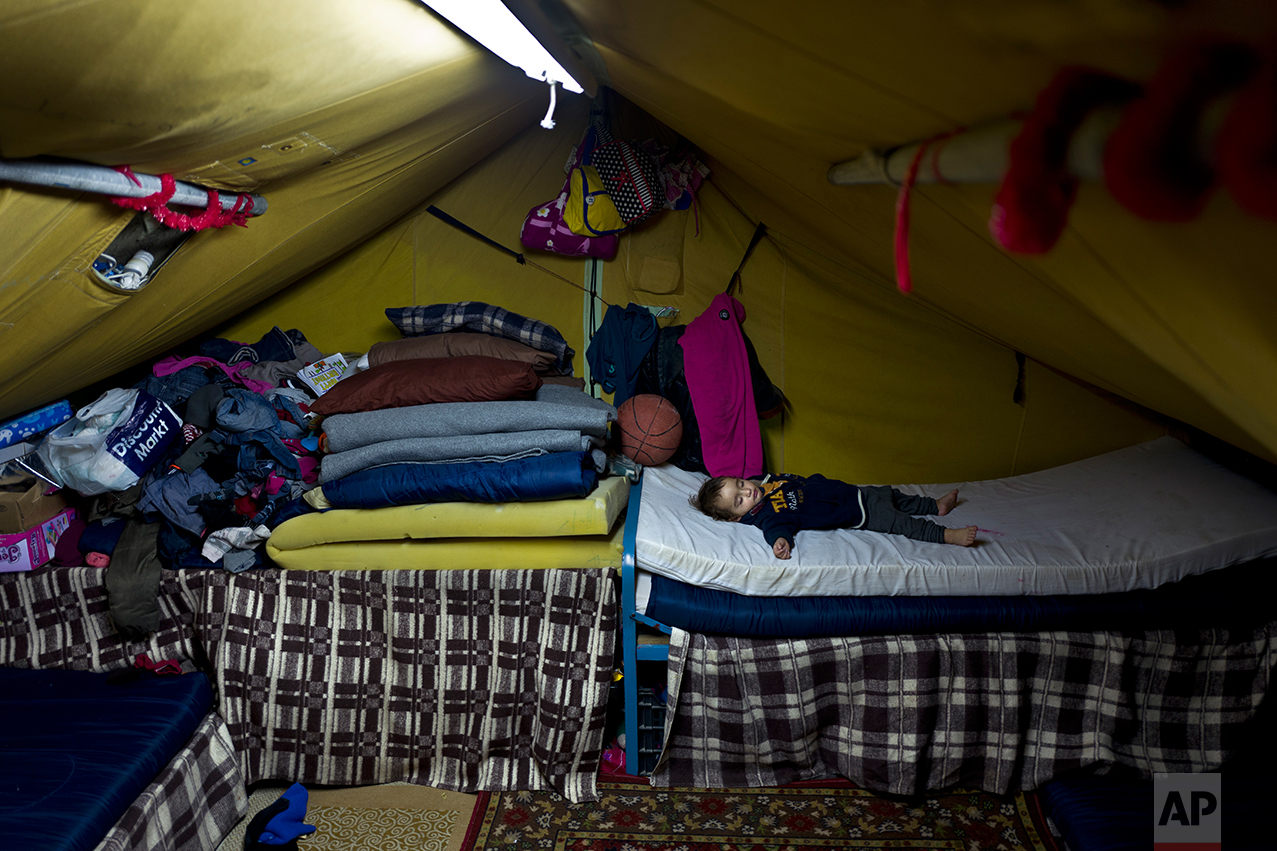 In this Thursday, Jan. 19, 2017 photo, Syrian refugee Elan Darwish, 14 months, sleeps inside his family's tent in Kalochori refugee camp on the outskirts of the northern Greek city of Thessaloniki. (AP Photo/Muhammed Muheisen)