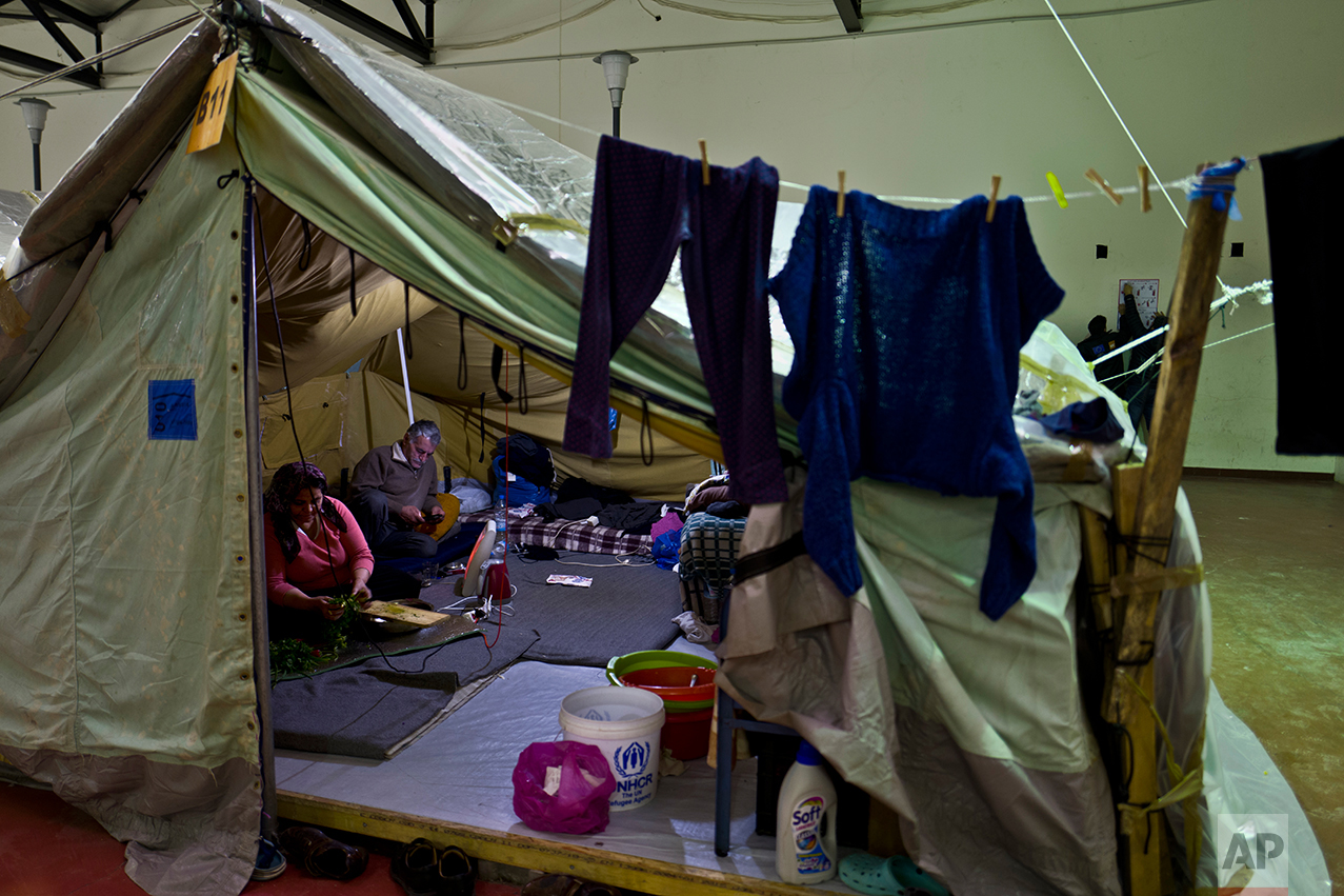 In this Tuesday, Jan. 17, 2017 photo, a Syrian refugee woman cuts vegetables while her husband checks his mobile phone at their tent in Kalochori refugee camp on the outskirts of the northern Greek city of Thessaloniki. (AP Photo/Muhammed Muheisen)