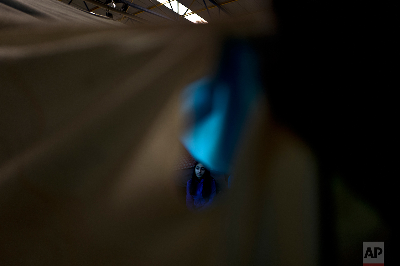 In this Wednesday, Jan. 18, 2017 photo, a Syrian refugee girl attends emotional support session provided to her and other refugees by volunteers from the Refugee Trauma Initiative, in a tent in Frakapor refugee camp on the outskirts of the northern Greek city of Thessaloniki. (AP Photo/Muhammed Muheisen)