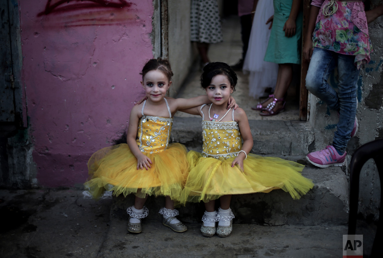 In this Saturday, July 30, 2016 photo, two girls pose for a picture as they sit in front of the family house during the wedding party of Palestinian groom Saed Abu Aser, in Gaza City. Weddings have emerged as a welcome celebration that slices through the often morose mood in the Gaza Strip, a Palestinian coastal territory run by the militant group Hamas. For both poor and well-off Gazans, weddings are a days-long, lavish affair of parties and dancing. (AP Photo/ Khalil Hamra)