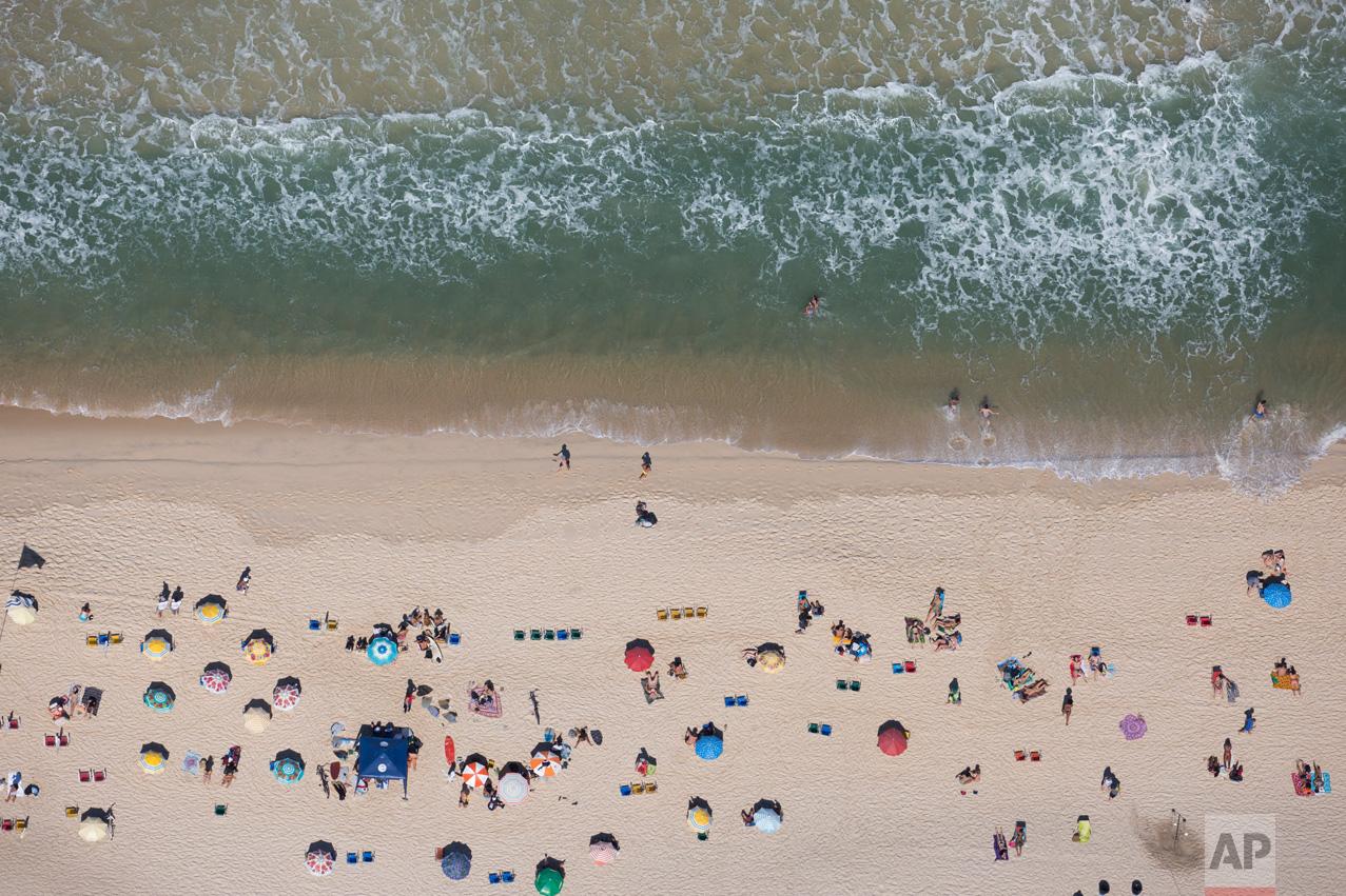 People sunbathe at Ipanema beach in Rio de Janeiro, Brazil, Monday, Aug. 1, 2016. The Summer Games start Aug. 5. (AP Photo/Felipe Dana)