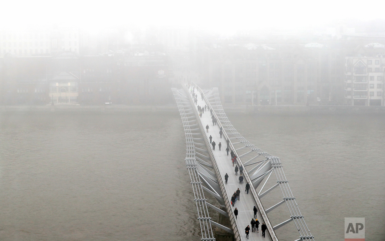 Pedestrians walk over the Millennium Bridge as fog shrouds St Paul's Cathedral in London, Monday, Jan. 23, 2017. Freezing fog covered the capital on Monday as cold weather conditions continued. (AP Photo/Kirsty Wigglesworth)