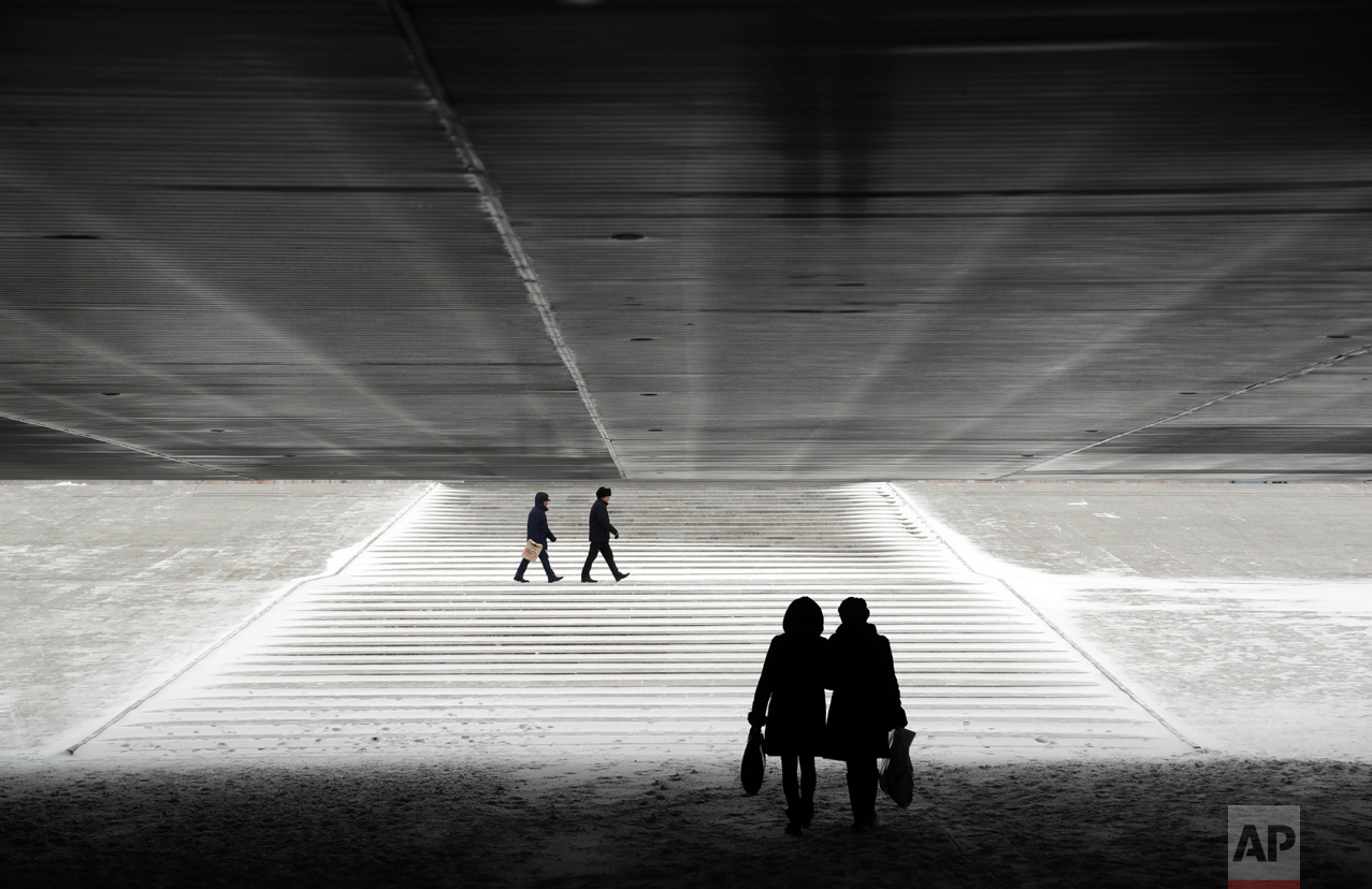People walk through an underpass in Astana, Kazakhstan, Wednesday, Jan. 25, 2017. The Kazakh capital was hit by a heavy gale and a snowfall with a temperature of - 6 C (F 21). (AP Photo/Sergei Grits)