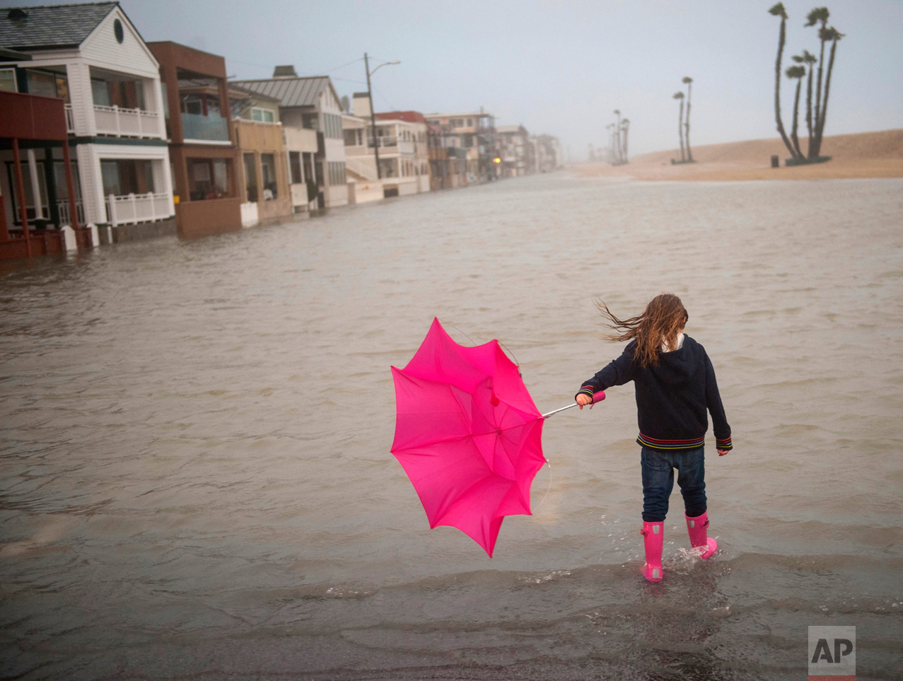 Isabella Busse, 6, holds an umbrella as she walks through floodwaters near the a pier during a storm in Seal Beach, Calif., Sunday, Jan. 22, 2017. The heavy downpour on Sunday drenched Orange County in one of the heaviest storms of the year. (Ana Venegas/The Orange County Register via AP)