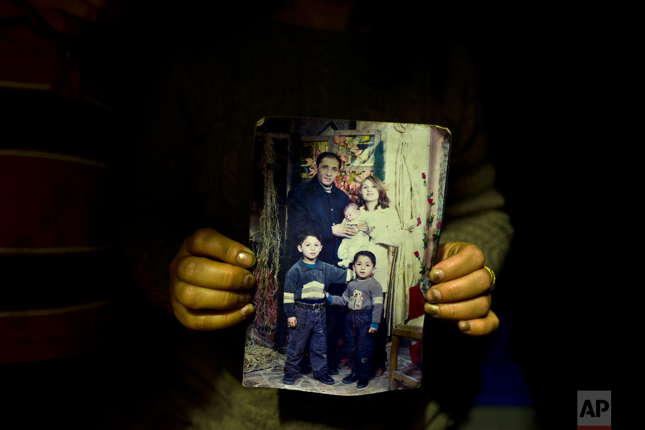 "In this Thursday, Jan. 19, 2017 photo, Fidan Kiru, 31, a Syrian refugee from Afrin, holds a photograph taken in 2004 showing herself and her husband Mohyeddin, when he was 27-years-old, and her sons, younger to older, Avindar, 8 months, Khalid, 4 and Levant, 6, at her tent in Kalochori refugee camp on the outskirts of the northern Greek city of Thessaloniki. ""This is the only group family picture we have, my husband is currently in Germany and I hope they will allow me to join him."" Fidan said. (AP Photo/Muhammed Muheisen)"