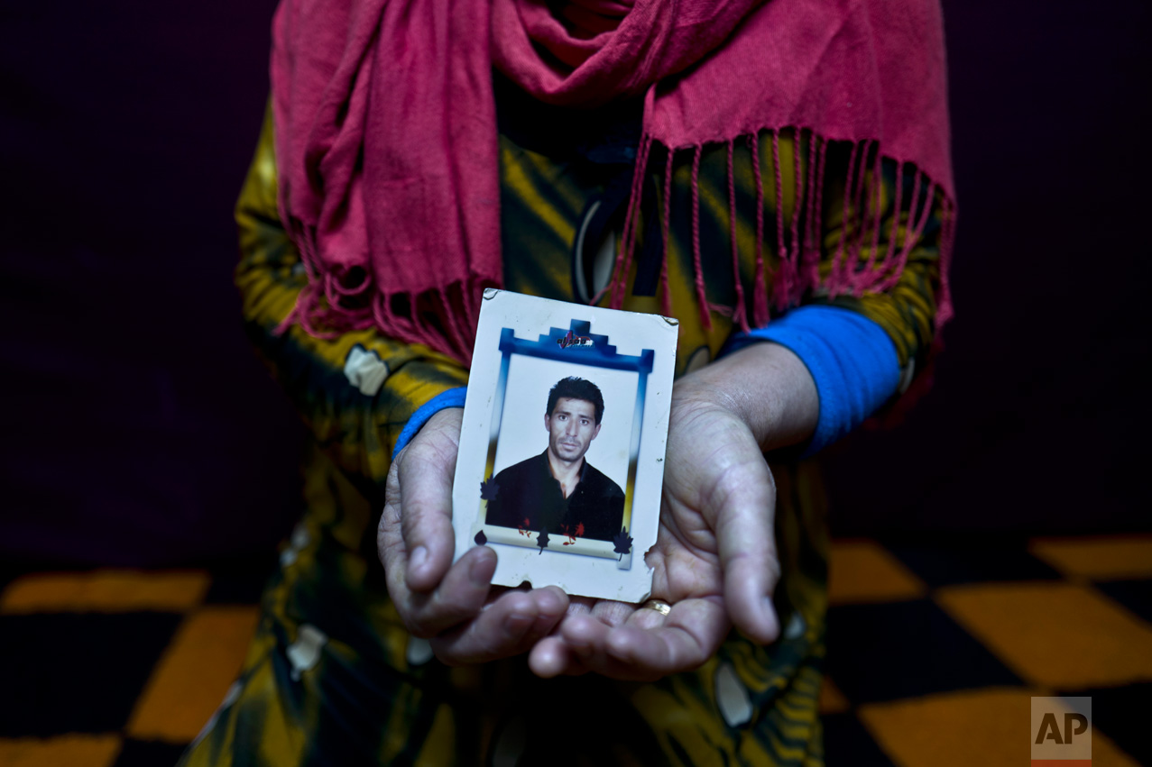 "In this Tuesday, Jan. 24, 2017 photo, Heven Daood, 39, a Syrian refugee from Tell-Tawil in al-Hasaka, shows a photograph of her husband Reiad, 45, at her shelter in Ritsona refugee camp, Greece. ""I have this photograph with me for the last 10 years, it is a very precious picture, my husband used to travel a lot for work, and this image always remained close to my heart."" Heven said. (AP Photo/Muhammed Muheisen)"