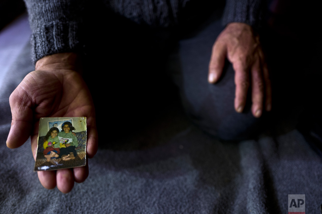 "In this Thursday, Jan. 19, 2017 photo, Ibraheem Ghareeb, 55, a Syrian refugee from al-Zohour Street in Aleppo, shows a photograph of his daughters, Mariam, when she was 7-years-old and currently 20 and lives in Germany, and his late daughter Layla, 13, who passed away in 2004 back in Syria, at his tent in Kalochori refugee camp on the outskirts of the northern Greek city of Thessaloniki. ""This is the only physical memory that I have left of my late daughter Layla, and it never leave my sight."" Ibraheem said. (AP Photo/Muhammed Muheisen)"