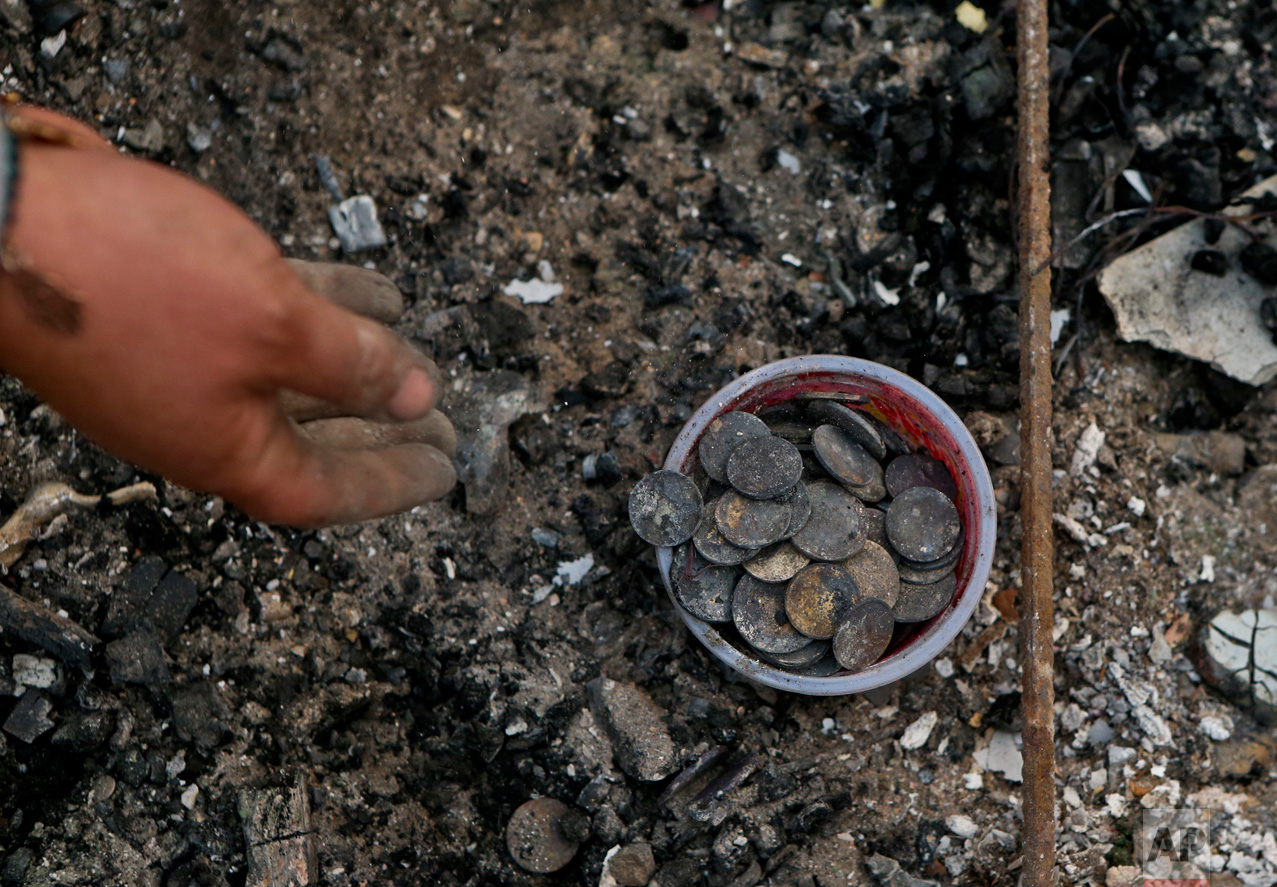 In this Thursday, Jan. 26, 2017 photo, Claudia Salinas salvages charred coins, which belong to her daughter, as she culls through the remains of their home destroyed by wildfires in Santa Olga, Chile. The flames engulfed the post office, a kindergarten, and about 1,000 homes in the town, located south of the Chilean capital. (AP Photo/Esteban Felix)
