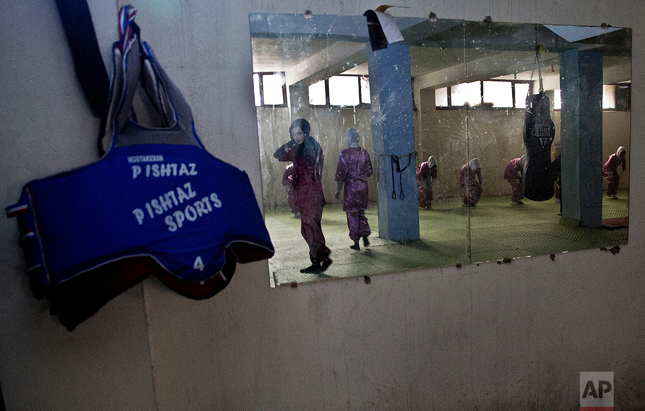 In this reflection Shaolin martial arts students train at their club in Kabul, Afghanistan, Tuesday, Jan. 25, 2017. When they aren't training on the snow covered hills that surround Kabul, the students train in a grungy, dark club financed by a young cinema actor. (AP Photos/Massoud Hossaini)