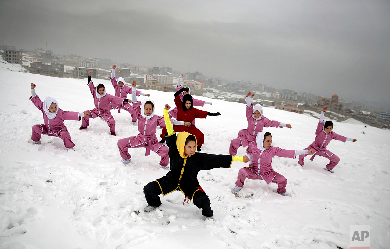 Shaolin martial arts students follow their trainer, Sima Azimi, 20, in black, during a training session on a hilltop in Kabul, Afghanistan, Tuesday, Jan. 25, 2017. Sima Azimi, 20, who is originally from Jaghuri in central Afghanistan, trains nine students in the martial arts to prepare for Olympic competitions, but also to protect themselves on the streets of Kabul, where women are routinely harassed. (AP Photos/Massoud Hossaini)