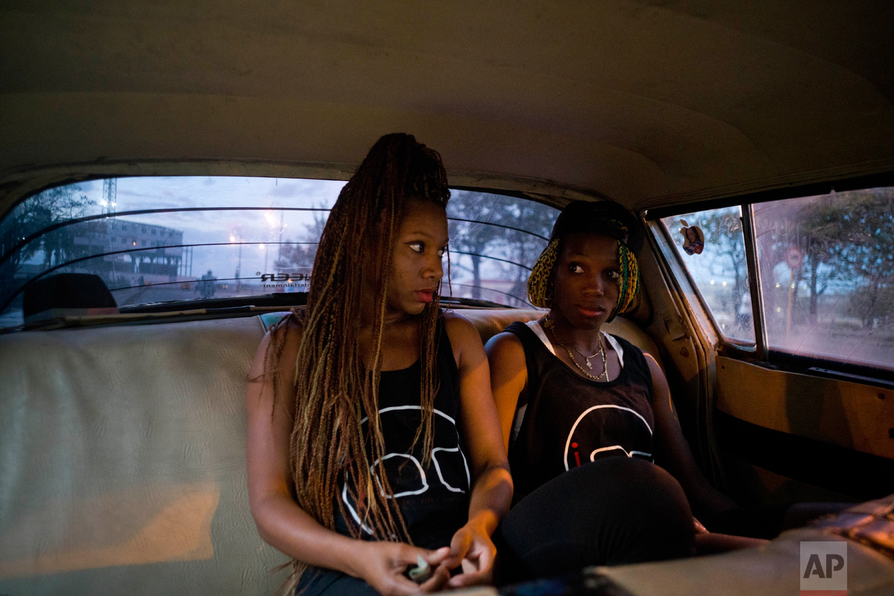 In this Jan. 30, 2017 photo, boxers Idamelys Moreno, left, and Legnis Cala, ride home in a taxi after training, in Havana, Cuba. Female athletes in Cuba have made strides in many other sports, including wrestling, judo and most recently, weightlifting, but not in boxing. (AP Photo/Ramon Espinosa)