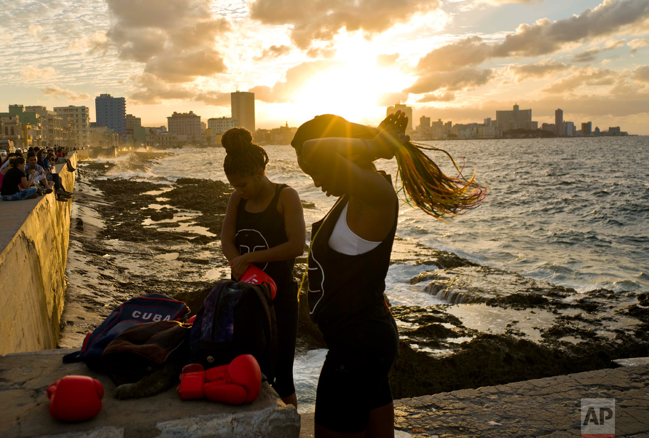 In this Jan. 30, 2017 photo, boxers Idamelys Moreno, left, and Legnis Cala, get ready for a photo session on Havana's Malecon, in Cuba. Moreno trains at least two hours a day after she gets off work, completing a routine that includes running several miles, lifting weights, hitting a punching bag and sparring with both women and men. (AP Photo/Ramon Espinosa)