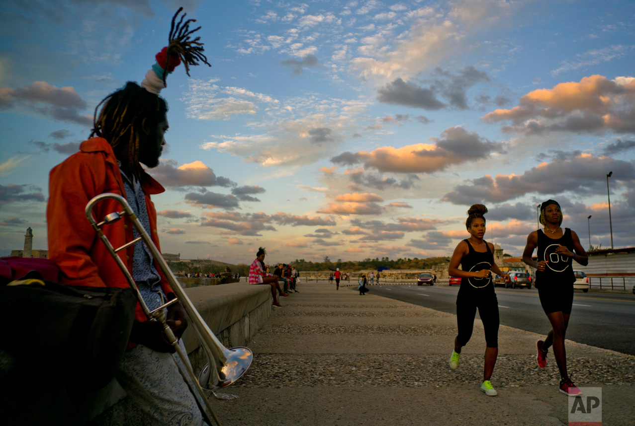 """In this Jan. 30, 2017 photo, boxers Idamelys Moreno, second right, and Legnis Cala, right, run along Havana's Malecon, in Cuba. Moreno and Cala are part of a group of up-and-coming female boxers on the island who want government support to form Cuba's first female boxing team and help dispel a decades-old belief once summed up by a former top coach: """"Cuban women are meant to show the beauty of their face, not receive punches."""" (AP Photo/Ramon Espinosa)"""