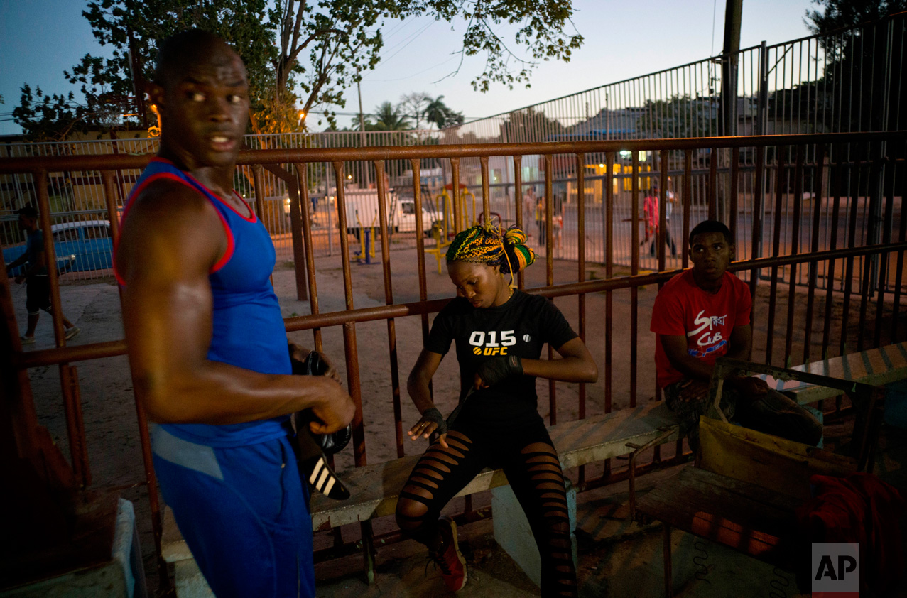 """In this Jan. 24, 2017 photo, Olympic silver medalist Emilio Correa Jr., left, mentors female boxer Legnis Cala, center, at a sports center in Havana, Cuba. """"They can bring more glory to the Cuban sport,"""" Correa said. """"They are diamonds in the rough. The motor skills, the explosive nature and the energy of Cuban boxers are also present in these women."""" (AP Photo/Ramon Espinosa)"""