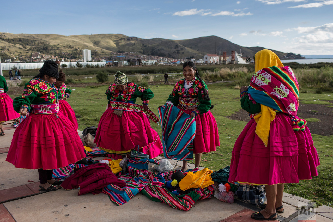 In this Jan. 29, 2017 photo, dancers put on their costumes near the shore of Lake Titicaca prior to their performance for Virgin of Candelaria celebrations in Puno, Peru. Some competing groups wear shoes made with alpaca skin, collars hung with ears of corn and hats adorned with old coins or the bright-colored feathers of Amazonian birds. (AP Photo/Rodrigo Abd)
