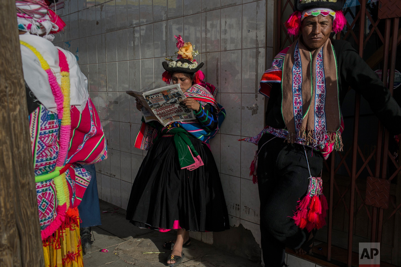 In this Jan. 29, 2017 photo, a dancer reads a newspaper while waiting to perform during Virgin of Candelaria celebrations in Puno, Peru. As many as 40,000 villagers are expected to gather for the annual festival and show their respect for the patron saint of the communities along the shores of Lake Titicaca. (AP Photo/Rodrigo Abd)