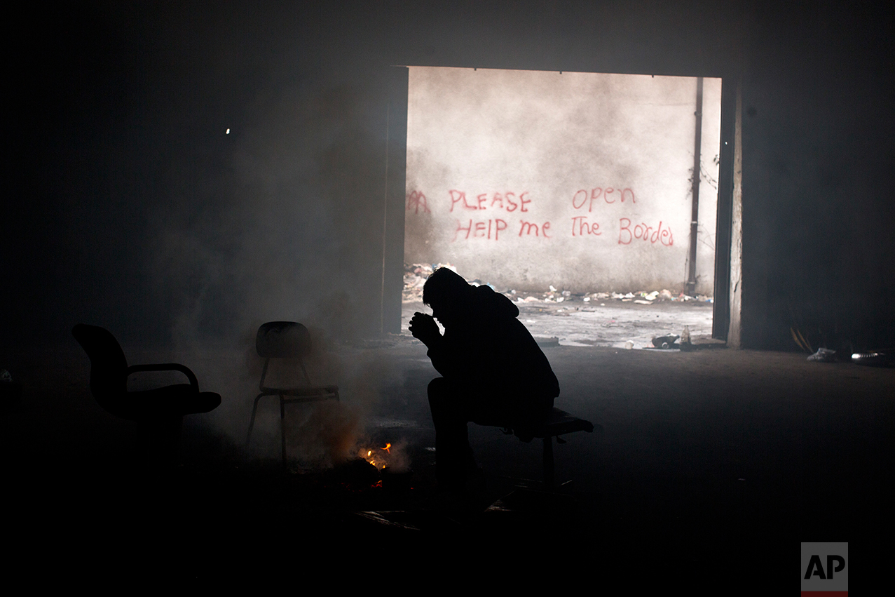 Refugee Samiuallah Ahmadi, 18, from Kabul, Afghanistan warms himself around a fire in an abandoned warehouse in Belgrade, Serbia, Saturday, Jan. 28, 2017. (AP Photo/Muhammed Muheisen)