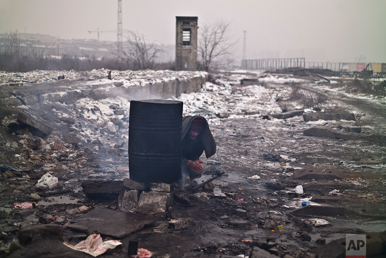 An Afghan refugee man washes himself outside an abandoned warehouse where he and other migrants took refuge in Belgrade, Serbia, Sunday, Jan. 29, 2017. (AP Photo/Muhammed Muheisen)