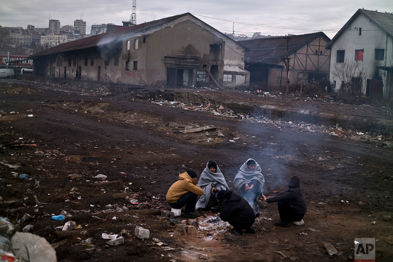 Migrants gather around a fire to warm themselves from the morning cold outside an abandoned warehouse where they are taking refuge, in Belgrade, Serbia, Thursday, Feb. 2, 2017. (AP Photo/Muhammed Muheisen)